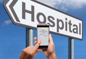 hospital sign with a phone in hand